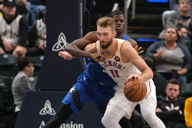 Indiana Pacers forward Domantas Sabonis (11) muscles under the defense of Orlando Magic center Mo Bamba during the first half of an NBA basketball game in Indianapolis, Saturday, Nov. 23, 2019.