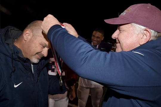 MRA head coach Herbert Davis receives his gold medal from Les Triplett after the Class 6A MSAIS State Football Championship on Saturday, November 23, 2019, at Mississippi College in Clinton, Miss.
