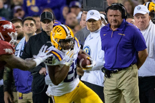 LSU coach Ed Orgeron watches running back Clyde Edwards-Helaire (22) carry against Arkansas during the first half of an NCAA college football game in Baton Rouge, La., Saturday, Nov. 23, 2019. (AP Photo/Matthew Hinton)