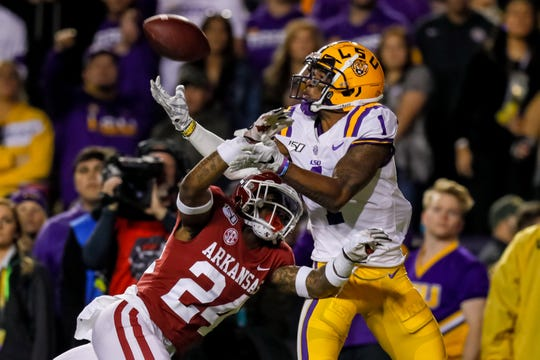 Nov 23, 2019; Baton Rouge, LA, USA; LSU Tigers wide receiver Ja'Marr Chase (1) catchers a touchdown pass over Arkansas Razorbacks defensive back LaDarrius Bishop (24) during the first half at Tiger Stadium. Mandatory Credit: Stephen Lew-USA TODAY Sports