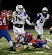 Otto Kuhns gets ready to pass the ball before being tackled during the Division IV regional final game Saturday. Bloom Carroll lost to Licking Valley 22-6 bringing their season to an end.