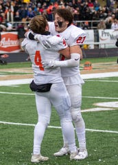 Nick Nemecek (4) and Brendan Mercier (27) celebrate following a 22-19 victory over Belleville in the state Division 1 football semifinals on Saturday, Nov. 23, 2019 at Howell.