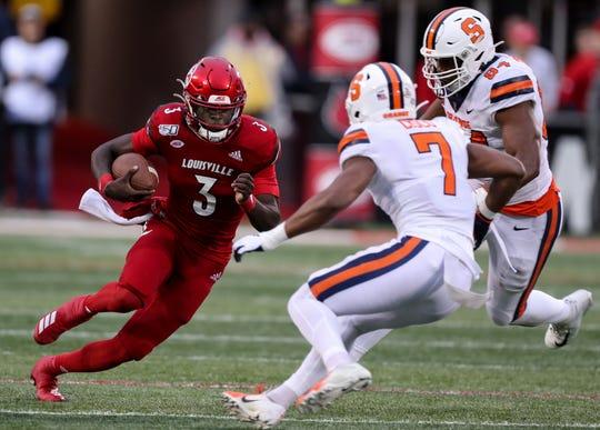 Louisville's Micale Cunningham breaks away from Syracuse defenders for a big gain on Nov. 23, 2019