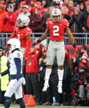 Ohio State defensive end Chase Young (2) and cornerback Jeff Okudah celebrate after the Buckeyes stop Penn State in the fourth quarter of Saturday's 28-17 victory.