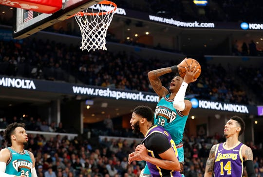 Grizzlies' Ja Morant (12) goes up at the net over Lakers' Anthony Davis (3) on Saturday, Nov. 23, 2019, during a game at FedExForum in downtown Memphis.
