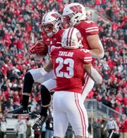 Badgers wide receiver Jack Dunn , middle, celebrates a touchdown catch with Wisconsin Badgers tight end Jake Ferguson (back) and running back Jonathan Taylor in the first half.