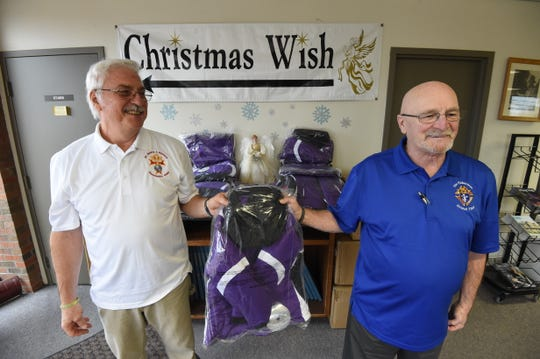 The Knights of Columbus members Robert Anderson (left) and Frank Holt (right) hold one of the coats the group donated to the Christmas Wish program Friday.
