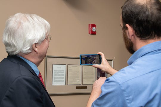 "Robert Arnold, the grandson of Air Force pioneer Gen. Henry ""Hap"" Arnold, looks on as a Muir S. Fairchild Research Information Center faculty member demonstrates the augmented reality capabilities at the library, Nov. 13, 2019, Maxwell Air Force Base."