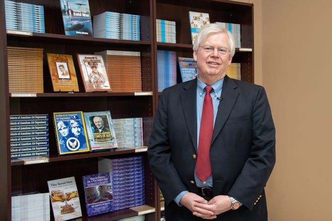 """Robert Arnold, the grandson of Air Force pioneer Gen. Henry """"Hap"""" Arnold, poses in front of a bookshelf at the Air University Press bookstore, Nov. 13, 2019, Maxwell Air Force Base,"""