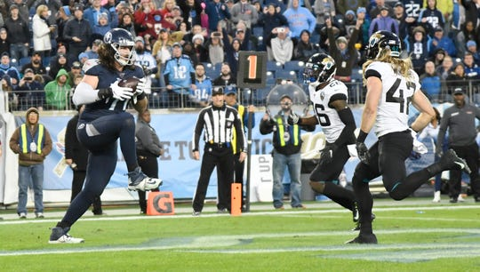 Titans offensive tackle Dennis Kelly (71) makes a touchdown catch during the third quarter Sunday.