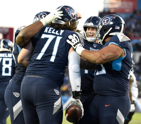 Titans offensive tackle Dennis Kelly (71) celebrates his touchdown catch during the third quarter Sunday.