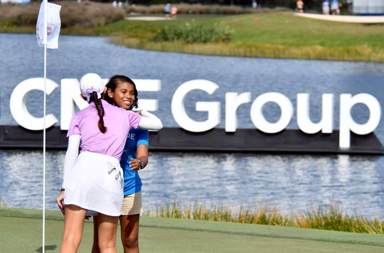 Cheyenne Knight hugs Mikayla Hylton a representative of St Jude on the 18th green after round of golf during the 2019 CME Group Tour Championship at the Tiburón Golf Club in Naples, Saturday, Nov. 23, 2019.