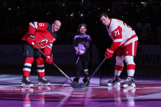 Nov 23, 2019; Newark, NJ, USA; Cancer survivor Grace Eline of Morris County  drops the ceremonial puck between New Jersey Devils defenseman Andy Greene (6) and Detroit Red Wings center Dylan Larkin (71) at Prudential Center.