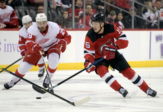 New Jersey Devils center John Hayden (15) skates with the puck as he is pursued by Detroit Red Wings left wing Brendan Perlini (29) during the second period of an NHL hockey game Saturday, Nov. 23, 2019, in Newark, N.J.