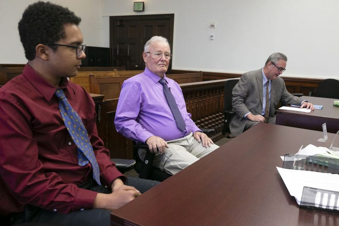 Richard Kendall looks on alongside his grandson, James Kendall, at the final adoption proceeding for Richard to adopt James at Maricopa County Superior Court in Phoenix on Nov. 30, 2018. Brian Salata (right), James' adoption attorney, reads during the proceedings. James and his two brothers, Ryder, 10, and Kevin, 9, were removed because of neglect from their mother, who was a drug addict and committed other crimes. Richard was unable to adopt Ryder and Kevin but has permanent guardianship of them.