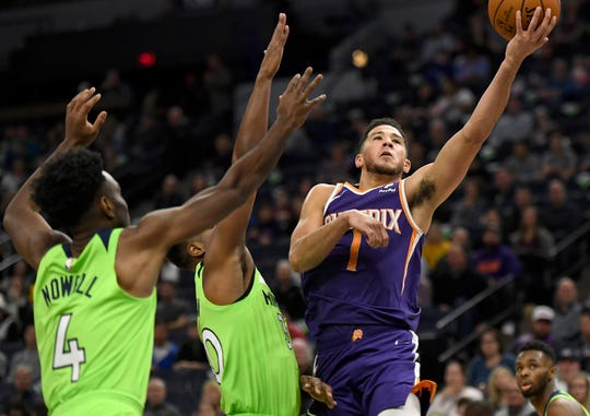 Phoenix Suns guard Devin Booker (1) shoots a layup as Minnesota Timberwolves' Jaylen Nowell (4) and Kelan Martin defend during the first quarter of an NBA basketball game on Saturday, Nov. 23, 2019, in Minneapolis. The Suns won 100-98. (AP Photo/Hannah Foslien)