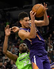 Phoenix Suns' Devin Booker (1) reaches for a rebound next to Minnesota Timberwolves' Andrew Wiggins (22) in the final minute of an NBA basketball game Saturday, Nov. 23, 2019, in Minneapolis. The Suns won 100-98. (AP Photo/Hannah Foslien)
