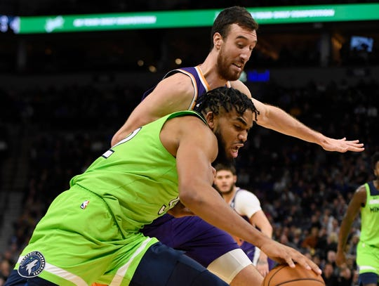 Phoenix Suns' Frank Kaminsky, behind, guards Minnesota Timberwolves' Karl-Anthony Towns during the fourth quarter of an NBA basketball game Saturday, Nov. 23, 2019, in Minneapolis. The Suns won 100-98. (AP Photo/Hannah Foslien)