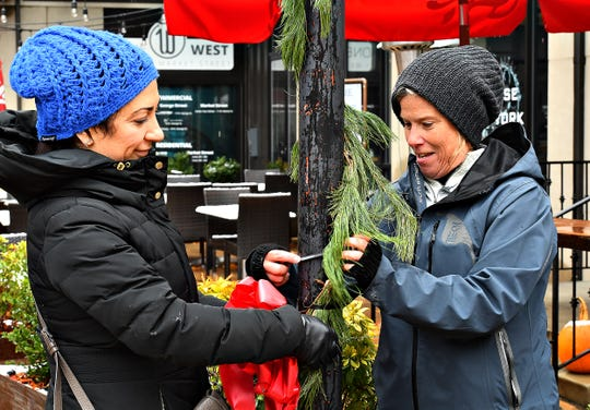 Yana Warner, left, of New Cumberland, and Sherri Ierley, of East Berlin, work to secure greens and a bow to a lamp post in Continental Square during the annual Hanging of the Greens in York City, Sunday, Nov. 24, 2019. The two were part of a group volunteering with York County Economic Alliance. Dawn J. Sagert photo