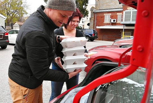 Brad Bokansky, left, and Amy Matulaitis, both of York City, fill their trunk with meals to  be delivered during Thanksgiving Community Dinner served at Union Lutheran Church in York City, Saturday, Nov. 23, 2019. Dawn J. Sagert photo