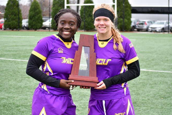 Juah Toe, left, poses with the trophy after West Chester University won the women's rugby national championship.