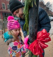Elora Wolfrays, 8, helps her father, David Gillespie, tie one last bow during the 18th Annual Hanging of the Greens in York. Some 150 lampposts were decorated throughout the downtown.