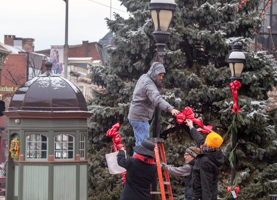 Volunteers decorate downtown York against a backdrop of the trolly kiosk and soon to be decorated Christmas tree during the 18th Annual Hanging of the Greens in York.