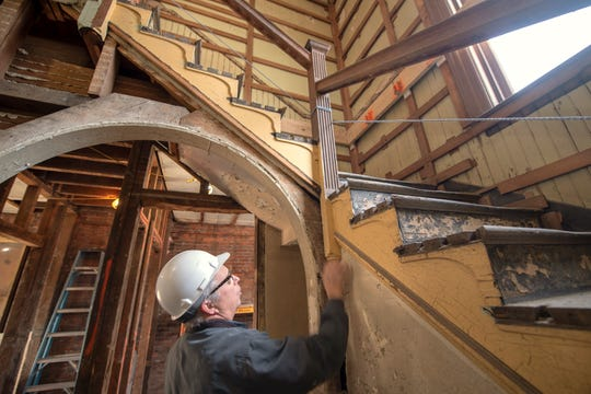 The Western Maryland Railway Freight Station is being renovated on North George Street in York. Project manager Don Bergens considers how the original first-floor banister will be raised to meet ADA compliance while retaining the historical characteristics of the staircase.