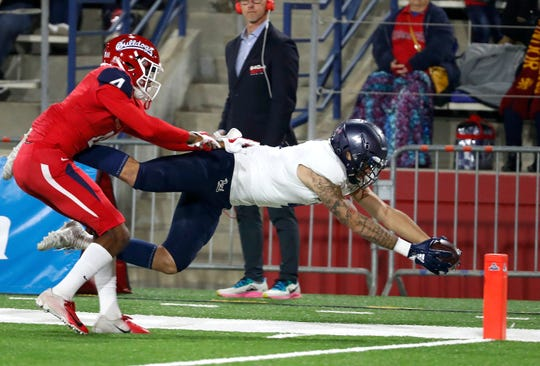 Nevada receiver Elijah Cooks dives for a touchdown past Fresno State defensive back Wylan Free during the Wolf Pack's win Saturday night.