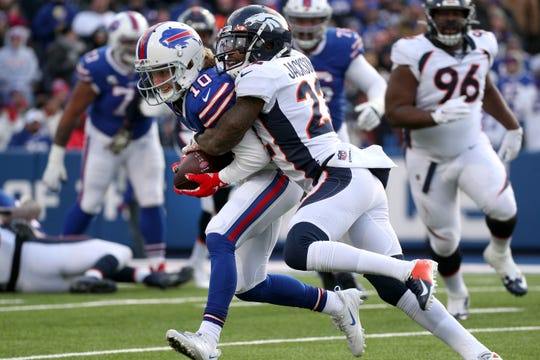 Bills receiver Cole Beasley is tackled by Denver's Kareem Jackson after a catch.