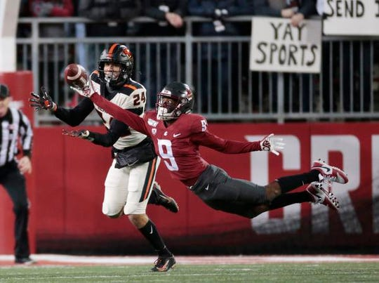 PULLMAN, WASHINGTON - NOVEMBER 23: Renard Bell #9 of the Washington State Cougars attempts to catch a pass against David Morris #24 of the Oregon State Beavers in the first half at Martin Stadium on November 23, 2019 in Pullman, Washington. (Photo by William Mancebo/Getty Images)