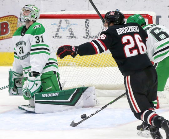 UND goalie Adam Scheel reacts to Jack Ahcan's goal in the first period as SCSU's Easton Brodzinski celebrates  in Saturday's NCHC game at the Ralph Engelstad Arena in Grand Forks.