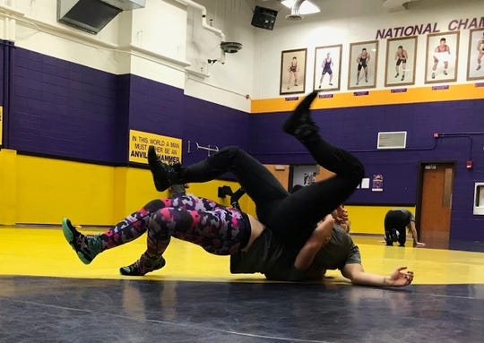 Brooke Thurber's legs fly into the air as she wrestles a teammate during an Oct. 22, 2019, practice at the wrestling facility at University of Wisconsin-Stevens Point, Wis.