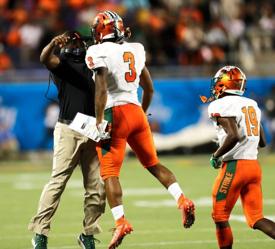 FAMU head coach head coach Willie Simmons chest bumps wide receiver Azende Rey (3) after he scored a touchdown during the Florida Blue Florida Classic at Camping World Stadium on Saturday, Nov. 23, 2019.
