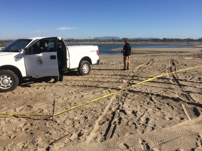Authorities investigate the scene where a body was found Sunday near the mouth of the Santa Clara River.