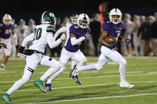 New Rochelle's Gary Phillips III (4) looks back a Shenendehowa defender as he runs for a second half touchdown during the NYSPHSAA Class AA state semifinal at Middletown High School Nov. 23, 2019. New Rochelle won the game 24-17.