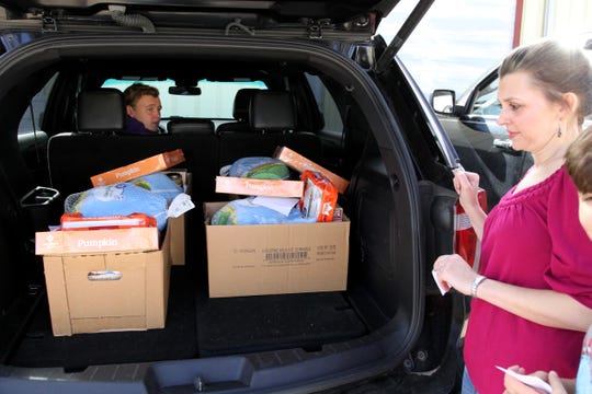 Sarah Cook finishes packing Thanksgiving baskets in her car to deliver them with the Wichita Falls Police Officers Association Sunday, Nov. 24, 2019.