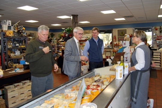 Gov. Evers, center, chats with Dawn Bechel as he and other members of the tour group sample the products inside the retail section of Eau Galle Cheese Factory.