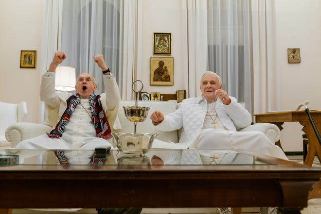 "Popes Francis (Jonathan Pryce, left) and Benedict (Anthony Hopkins) bond over World Cup soccer in ""The Two Popes."""