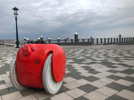 A cargo-carrying robot called the Gita sits near a waterfront park on Monday, Nov. 11, 2019, in Boston. A subsidiary of Italian automaker Piaggio designed the machine to follow its owner carrying groceries and other items. (AP Photo /Matt O'Brien)