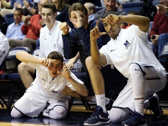 Members of the Monmouth Bench Mob mimic photographers covering the Monmouth University Hawks' 73-54 win over Wagner on Dec. 13, 2015 in West Long Branch.