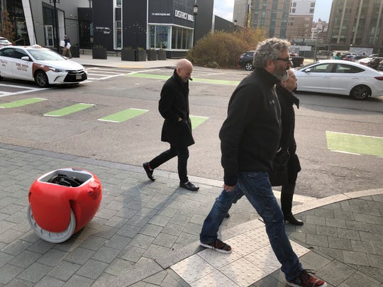 Piaggio Fast Forward CEO Greg Lynn, center, is followed by his company's Gita carrier robot as he crosses a street on Monday, Nov. 11, in Boston. The two-wheeled machine is carrying a backpack and uses cameras and sensors to track its owner. (AP Photo / Matt O'Brien)