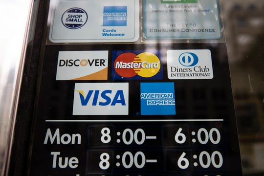 This Thursday, Nov. 29, 2018 file photo shows credit card logos posted on a store's door in Philadelphia. The SMART acronym calls for goals to be specific, measurable, assignable, realistic and time-related. (AP Photo/Matt Rourke, File)