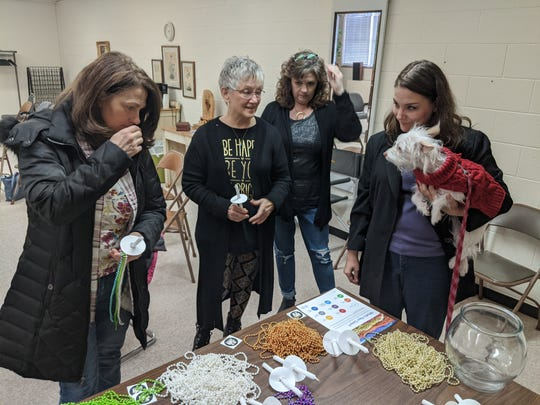 Samantha Manski, right, with emotional support dog Ollie, helps Gwyn Burns, left, Mitzi McAndrew and D'Nette Broyles select beads representing their own personal story during the candlelight vigil on International Survivors of Suicide Loss Day Nov. 23.