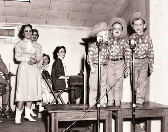 Dressed for a day on the West Texas prairie, the Gatlin boys - from left, Rudy, Steve and Larry perform from atop piano benches. Their mother, Billie, is at the piano. The boys first performed in Abilene 65 years ago next March.