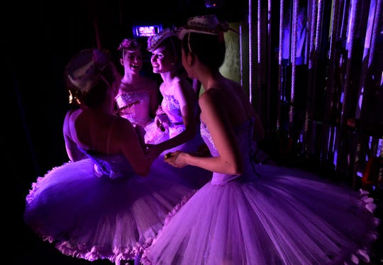 """Dancers share a moment in the wings of the Paramount Theatre before performing as Mirlitons during rehearsal for """"The Nutcracker"""" Wednesday. A mirliton is a musical pipe which the dancers pantomime playing during their performance."""