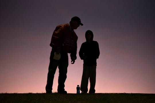 Bruce Marteen and his son Luke Marteen, 11, watch the Harper Creek vs Coldwater football game on Friday, Oct. 18, 2019 at Coldwater High School. Students wore purple jerseys for the charity Fight the Fight, which raises money for all types of cancer.