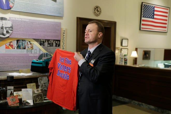 """Tim Eyman, a career anti-tax initiative promoter, holds up a t-shirt that reads """"Let the Voters Decide,"""" as he talks to reporters, Monday, Nov. 25, 2019, at the Capitol in Olympia, Wash. Eyman was in Olympia to officially announce his entry into the 2020 governor's race as an independent."""