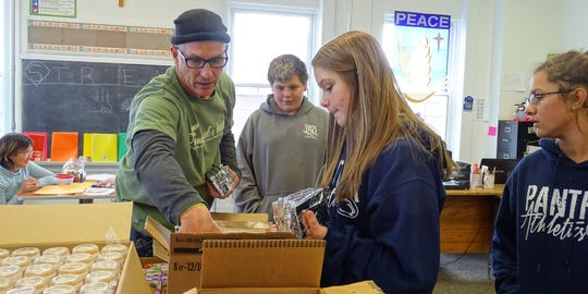 Students at St. Joseph Catholic School in Crestline help Tony Horning, left, pack food for Emmanuel's Bread. The nonprofit currently provides meals for 114 Crestline students but demand is growing.