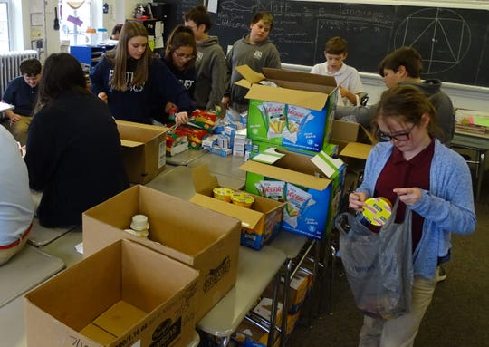 St. Joseph Catholic School students in Crestline help pack easy-to-serve meals for Emmanuel's Bread to provide to students in need.